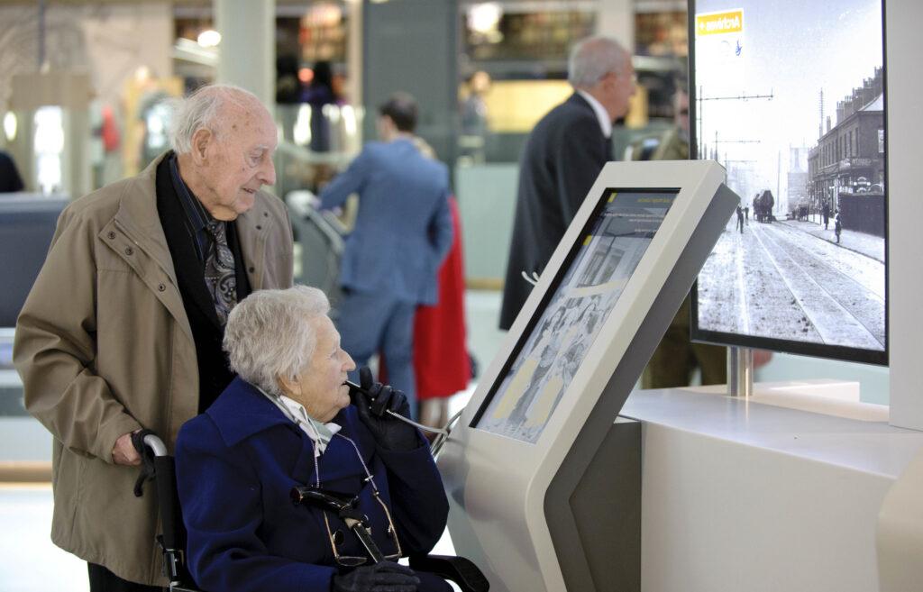 Elderley couple looking at an interactive museum board