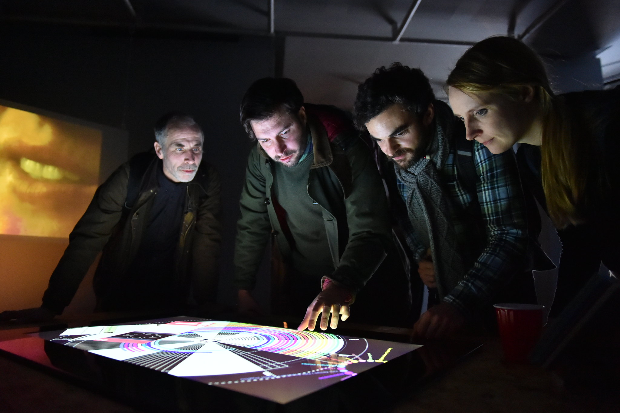 Four people gathered around touchscreen table.