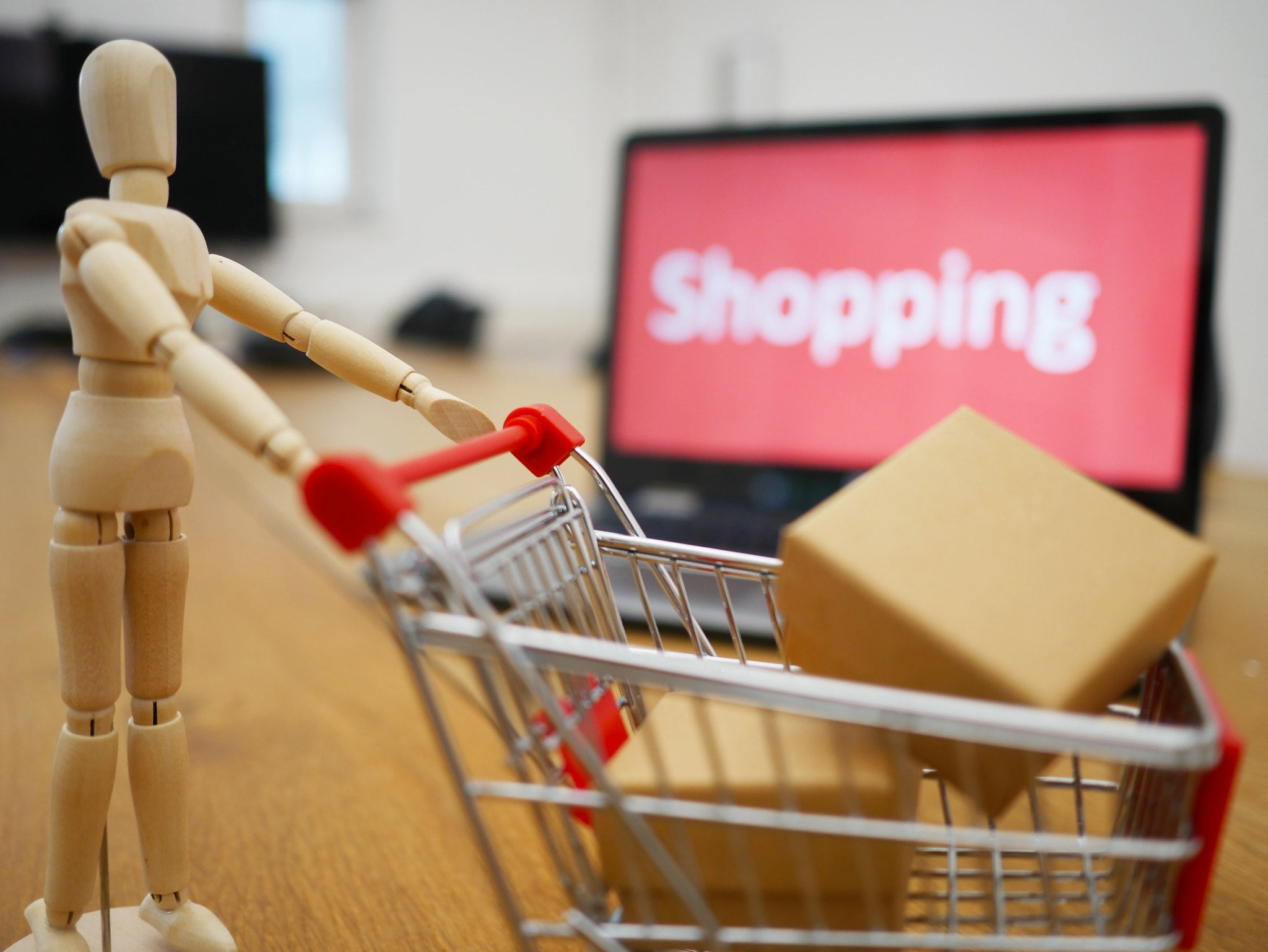 Figurine pushing a shopping trolley with laptop in background