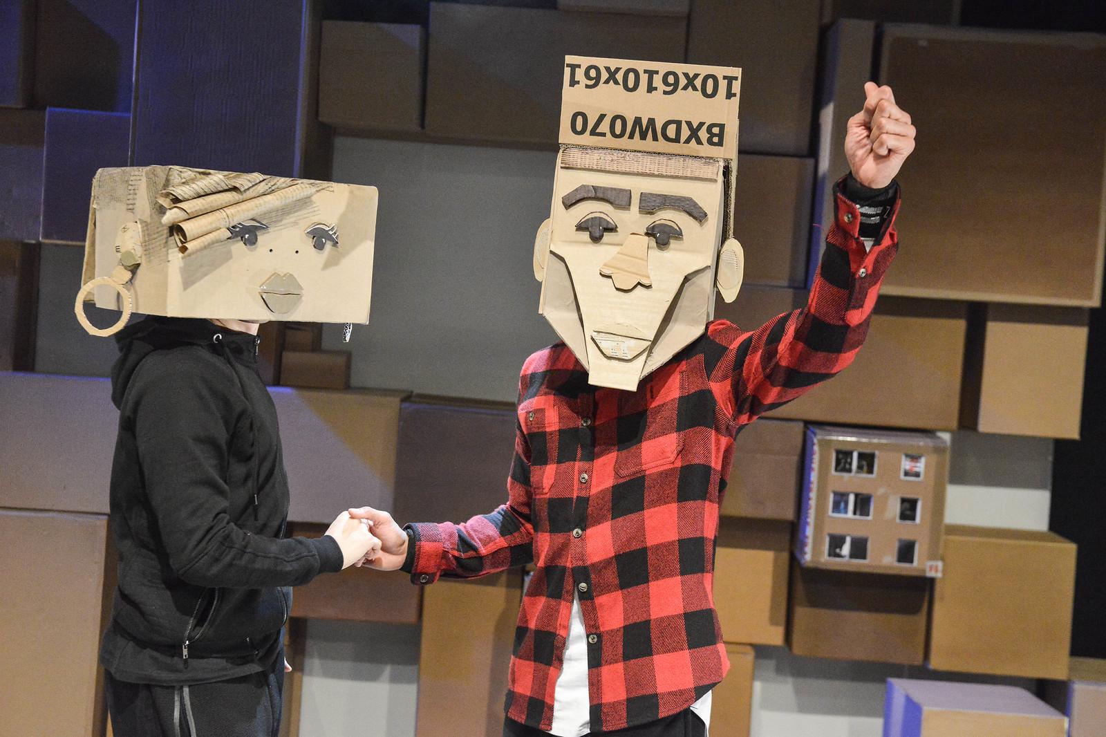 Two people wearing cardboard masks shake hands