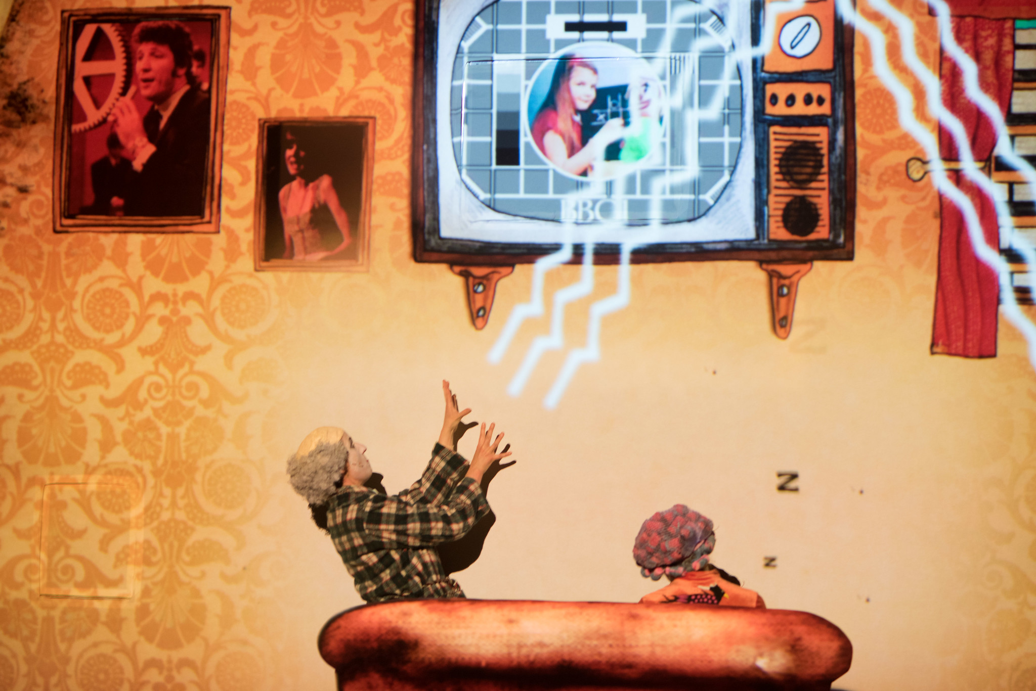 Artwork showing bolts of electricity between person and television screen
