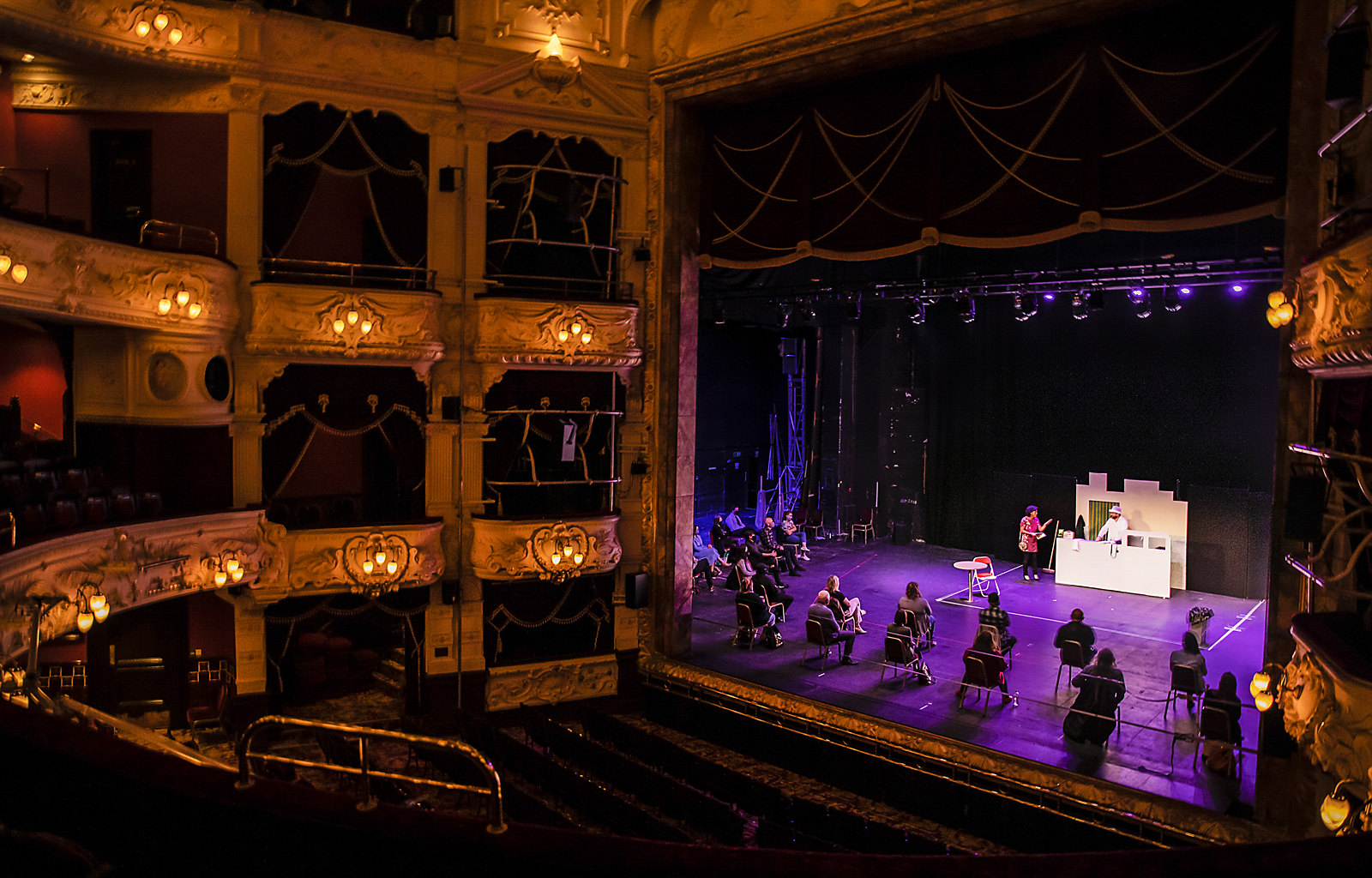 Performers on theatre stage in empty theatre