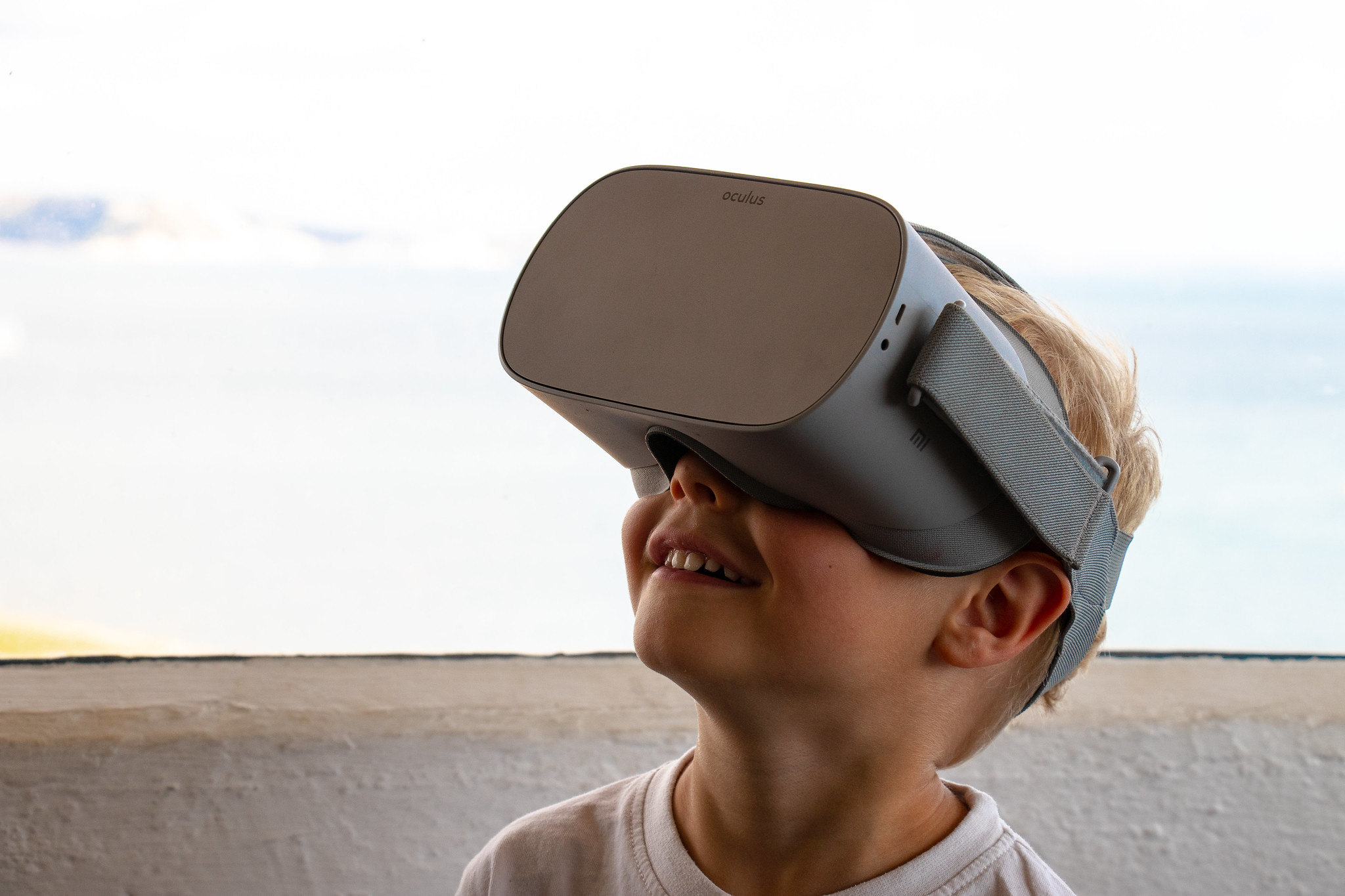 Young boy wearing a virtual reality eye mask on what looks to be the surface of the moon