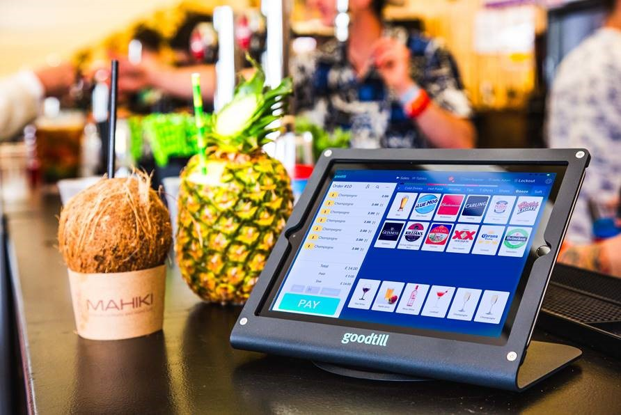 Image of laptop next to a pineapple and coconut containing drinks