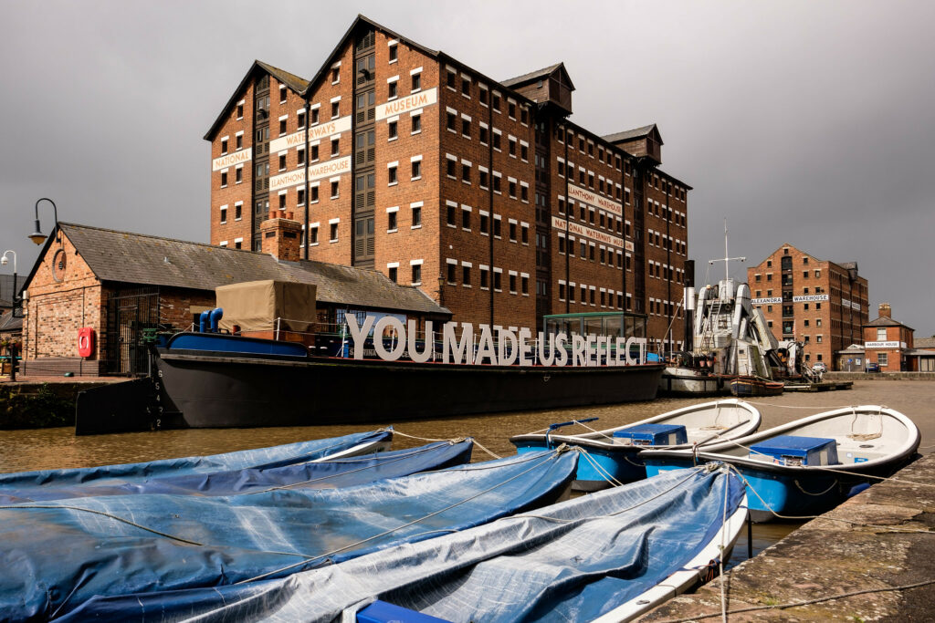 Image of an old factory building with a river and moored boats in the foreground. One boat shows the words 'you made us reflect'.