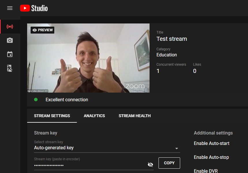 A screenshot of the Zoom Meeting feed in the YouTube Control Room. The video feed is of a man holding both thumbs up.