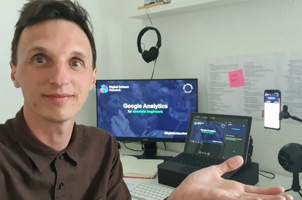 A man is facing the camera and gesturing to his home office desk set up, which features 2 computer screens side-by-side, as well as a mobile phone on a stand.