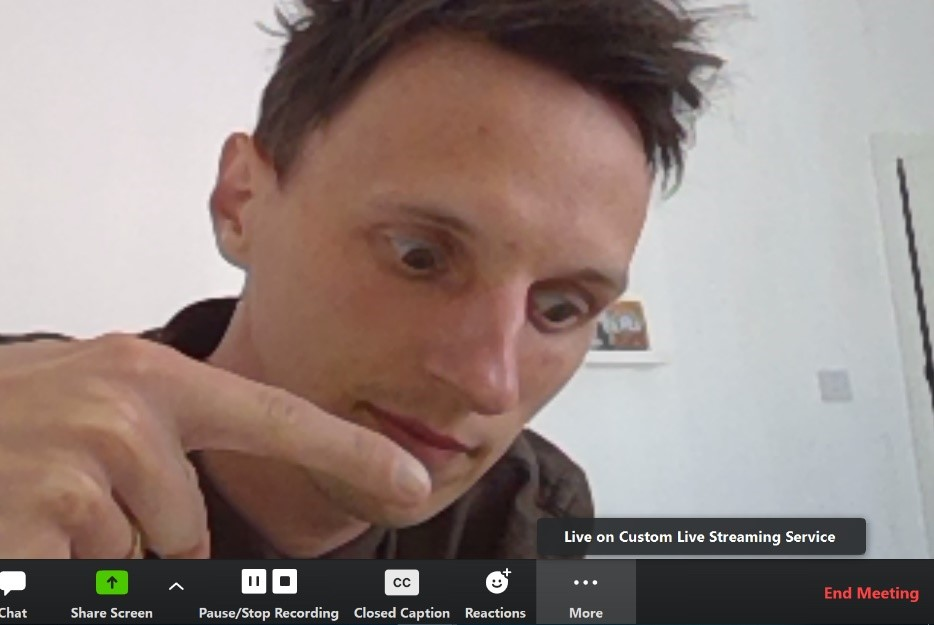 A screenshot showing a man's face. He is on screen in a Zoom Meeting. He is pointing to the Live on Custom Live Streaming Service button.